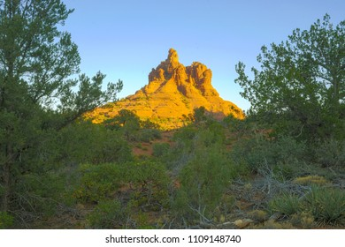 View to Bell Rock in the light of sunset sunlight framed  between two trees sitting in deep shade of evening light,, Sedona, Arizona, USA
