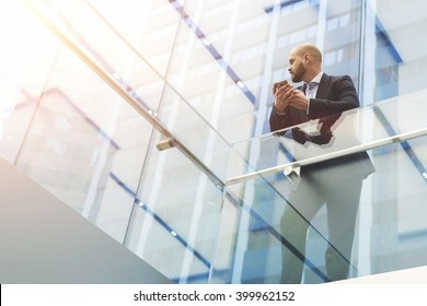 View from below of a businessman is holding mobile phone in hands, while is standing in skyscraper interior with modern design background with copy space for your advertising text message or content