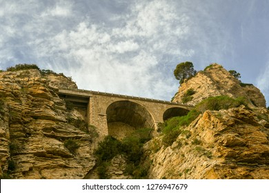 View from below of the cliff on the port of Alassio with the arches supporting the Aurelian Drive, Alassio, Liguria, Italy
