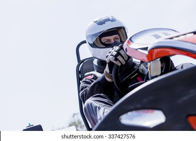 view from below of a concentrated gokart pilot on the starting line before starting a race in an outdoor go karting circuit - focus on the right eye