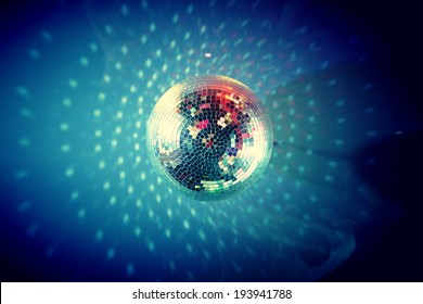 View from below of disco ball sparkling in darkness