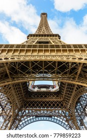 View from below of the Eiffel tower showing its lacy metallic structure and brown color under a blue sky with white clouds.