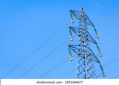 View from below of an electricity pylon supporting an overhead high-voltage power line against blue sky.