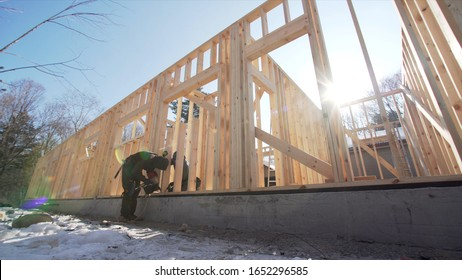 View from below of framers working at frame residential house building, attaching wooden planks. Sunny day