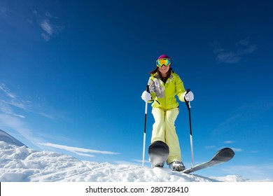 View from below of happy woman in mask  holding ski poles and ready to ski at Krasnaya polyana ski resort and Caucasus mountains in Sochi, Russia