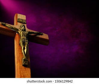 View from below of wood crucifix with gold body of Christ with beam of sunlight on digitally created purple and black mottled shades - concept of Lent and repentance
