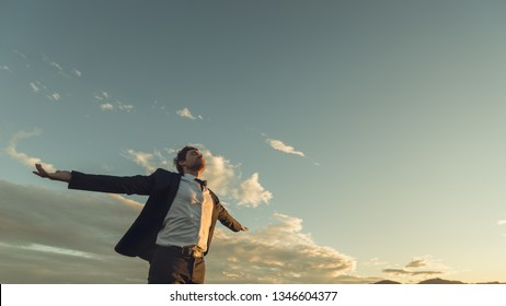 View from below of a young businessman in a suit enjoying his freedom and professional independence with arms wide open standing under evening sky.