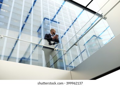 View from below of a young economist of a successful company is waiting for a call on mobile phone, while is standing in skyscraper office interior with modern design. Copy space for your text message