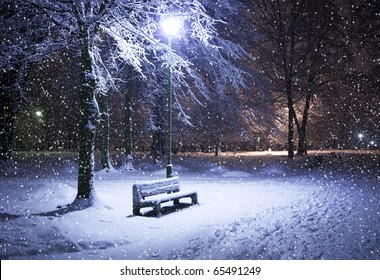 View of bench against christmas tree and shining lantern through snowing. Night shot.