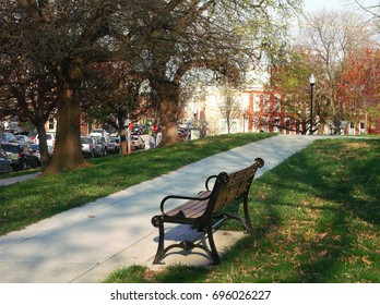 View of a bench in Riverside Park (Baltimore, MD) along sidewalk.  Photo gives view of Randall St.