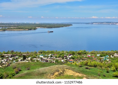 view of the bend of the Volga River from the hill, suburban and urban buildings, coastline, islands, green vegetation, tanker going along the river in the background, Saratov, Russia