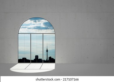 View of Berlin skyline out of big window in a concrete loft