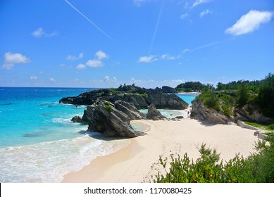 View of Bermuda beach and Horseshoe Bay with pink sands, blue water, blue sky, and large rocks jutting out.