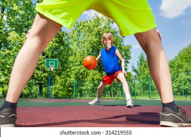 View between two legs of player and boy with ball