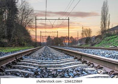 View between the two steel bars of a railroad track diminishing in the distance, in the Dutch province of Limburg, at sunset