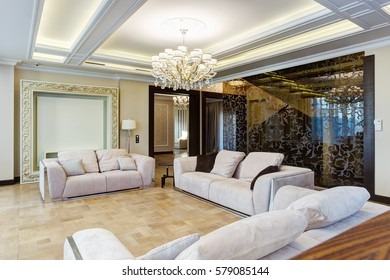 View of big and light living room with three cozy sofas with pillows for big family and chandelier in center of ceiling. Luxury interior with element of glasses and wood in white, beige, brown colors.