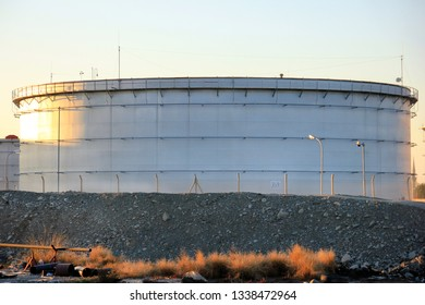 View of the big oil storage tank with floating roof. Storage tanks are often cylindrical in shape, perpendicular to the ground with flat bottoms, and a fixed flangible or floating roof.