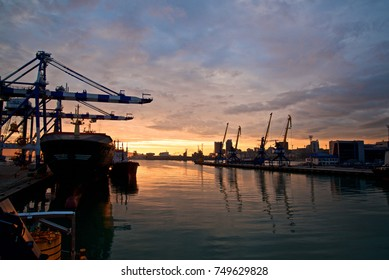 View of big seaport. Cranes and big vessels. Blue sky with clouds at sunset. Green water with beauty reflections.