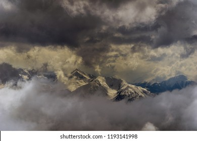 View to Big snow-capped Mountains surrounded by dark Clouds.