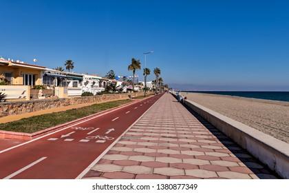 View of bike lane and beach promenade in Roquetas de Mar on the Mediterranean coast of Spain.