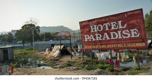 View of a billboard advertising 'Hotel Paradise' next to slums. The picture evokes feelings of social injustice. It was taken in February 2010 on a road close to Haridwar in India