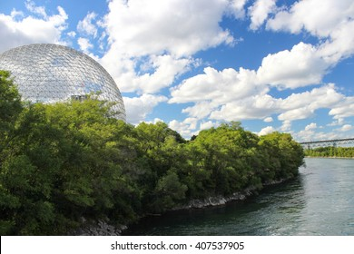 View of Biosphere on the Saint Helen`s Island in Montreal, with green park and blue, cloudy sky.