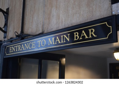 View of a black and gold pub sign showing direction to the main entrance