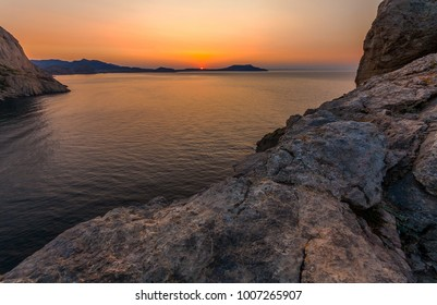 View of Black Sea bay, huge rock in front and mountains in distance in beginning of sunrise in Crimea
