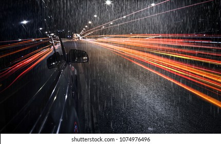 View of black SUV car parking on the  road during hard rain fall with  traffic light trails ,long shutter speed exposure.