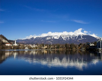 A view of the Bled and Slovenska alps covered with snow, reflection of nature in the lake