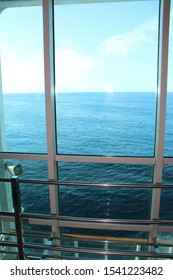 A view of the blue calm ocean looking out through a large cruise ship window with railings.