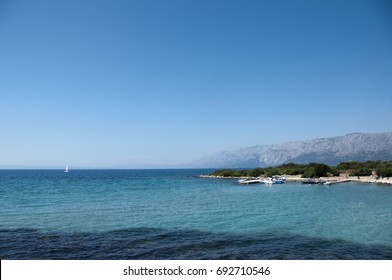 A view of the blue Croatian sea with hills in the background