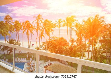 View from blue glass balcony from modern building. View to beautiful beach with palms and peoples during sunny day.