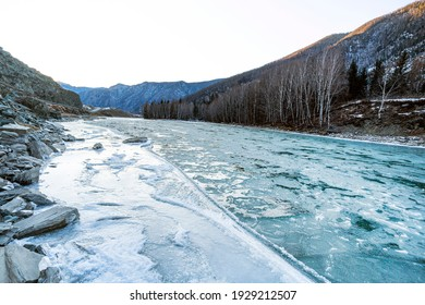 view of a blue and green river with snow and crushed ice during an ice drift in winter in the Altai mountains in Russia.
