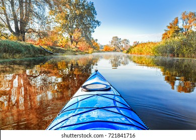 View from the blue kayak on the river banks with autumnal yellow leaves trees in fall season. The Seversky Donets river, autumn kayaking. Selective focus at nose kayak's part.