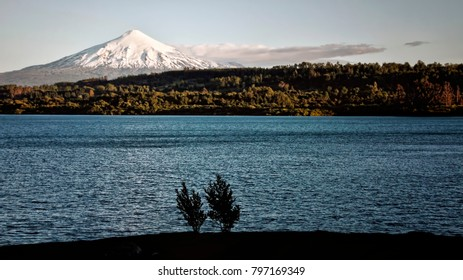 View of Blue Lake, Forest, and White Capped Volcano (Pucon, Chile).