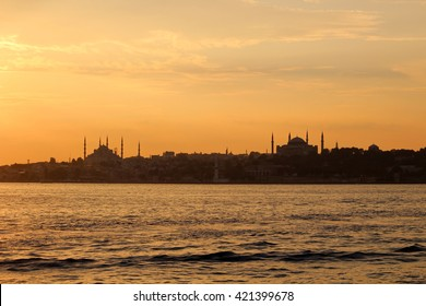View of the Blue Mosque and Hagia Sophia in Istanbul from the water at sunset