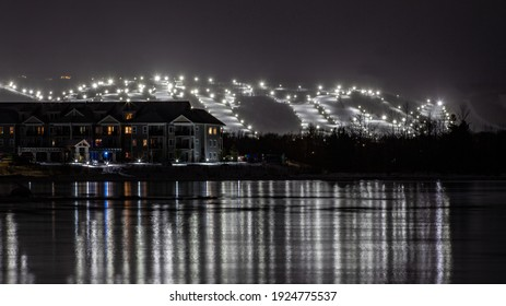 View of Blue Mountain ski resort and village from Lighthouse Point, Collingwood, Ontario. Ski runs are lit up for night skiing for skiers and snowboarders to ski at night during the winter