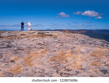 A view of the blue mountains in Syndey, Australia appear as two men approach the edge of a flat but textured and coloured stone cliff top