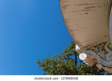 View of blue sky and magnolia tree from under a curved exterior balcony, copy space, horizontal aspect
