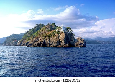 View from the blue waters of Ligurian sea of the Lighthouse of  Portofino on the peninsula closing the bay