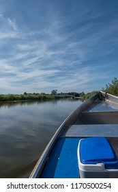 View from a blue whisper boat on a river in rural Groningen in the Netherlands on a hot sunny day