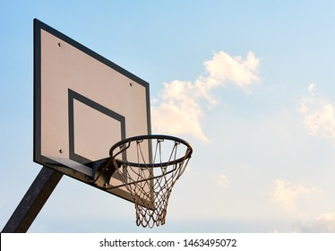 view of board with basketball hoop and net. Evening sky at sunset background.