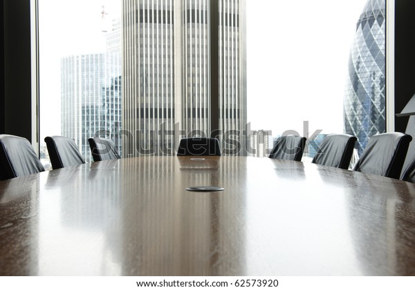 view of boardroom table with chairs and city buildings in background