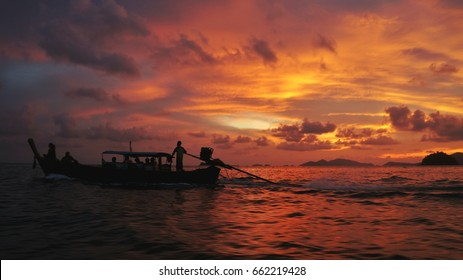 The view of a  boat against the light during the sunset in the ocean