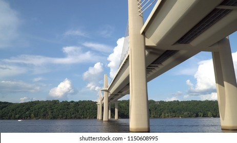 View from boat passing underneath bridge spanning over a river on a clear summer day. Modern construction engineering for road motorway to cross natural borders