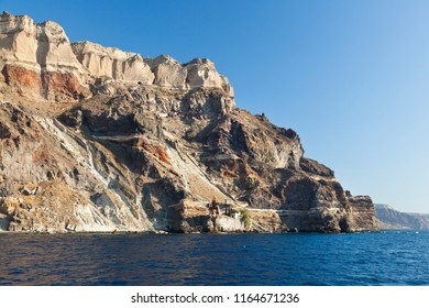 View from a boat to the southeastern crater wall of Santorini, Greece with some old industrial buildings for pumice export down at the coast.