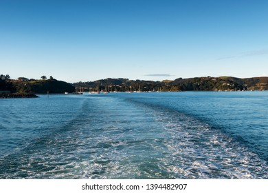 View of the boat wake out the back of a boat leaving Waiheke Island, New Zealand.