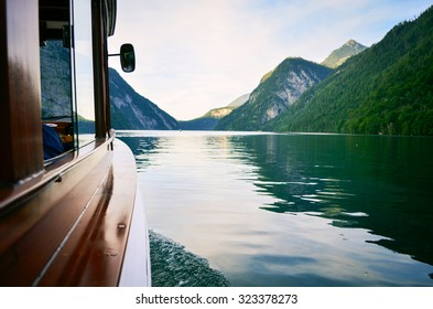 view from the boat window. Ferry is old and wooden. View on the Koningsee lake in Bavaria, Germany. Water and mountains on background