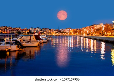 "View of boats and beautiful marina at night with super moon - Canakkale, Turkey ""Elements of this image furnished by NASA """